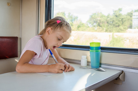 six year old: Six year old girl draws a pen on a sheet of paper in a second-class train carriage