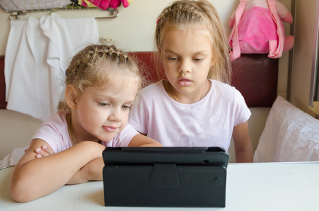 economy class: Two girls sisters sitting in the train watching cartoon Tablet PC Stock Photo