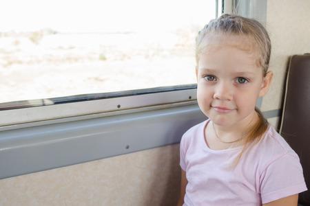 sedentario: Feliz niña de cuatro años se sienta en una silla junto a la ventana de un tren de cercanías eléctricos Foto de archivo