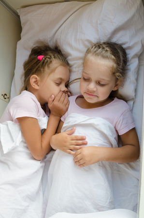 four classes: Two little girls sister sleep on a cot in a train Stock Photo