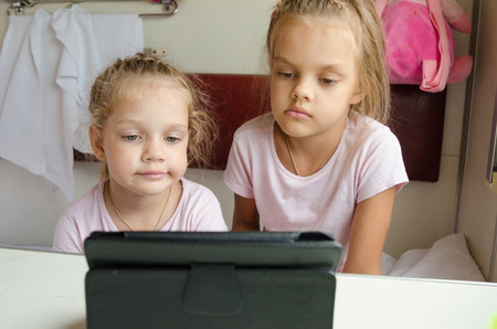 six year old: Two girls sisters sitting in the train watching cartoon Tablet PC Stock Photo