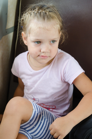 sits on a chair: four-year girl sits on a chair in the electric train