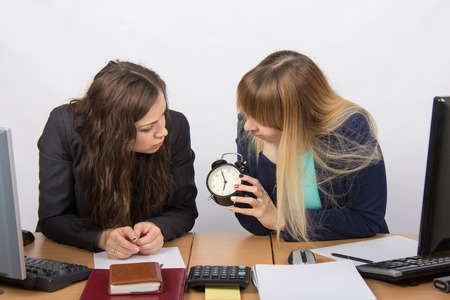 slacker: Two office workers at the end of the day looking at his watch Stock Photo