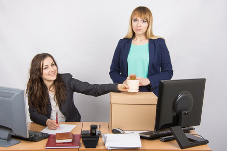 insincerity: Office worker happily helps collect things sacked colleague Stock Photo