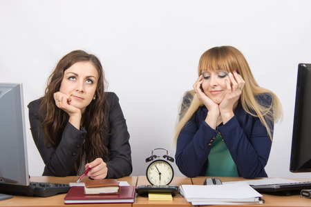slacker: Two bored office worker waiting for the end of the day and look at the clock