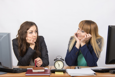 slacker: Two bored office worker waiting for the end of the day and look at each other Stock Photo