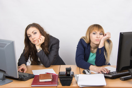 lethargy: Two young office employee wearily sitting behind a desk