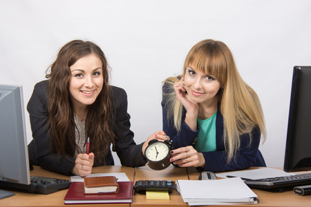 slacker: Two happy office workers checked against the clock at the end of the working day
