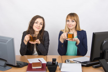 statutes: Two young beautiful girls drink tea, office behind a desk in transparent glasses Stock Photo