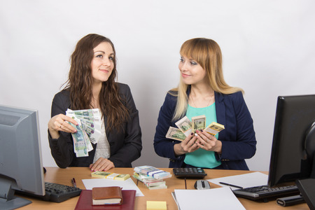 collaborators: for office table two women collaborators happily hand-held fan of bundles of money, and discuss them dreamily Stock Photo
