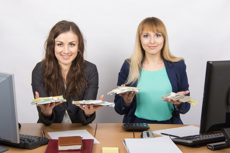 venality: for office table two women collaborators happily looking at a lot of money on the table