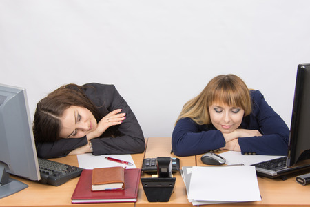 drowsiness: Two young office employee asleep on desk for computers