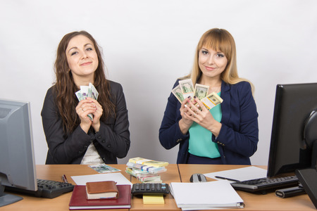collaborators: for office table two women collaborators happily cuddle a lot of money on the table