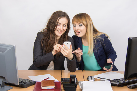 Two young office employee engaged in private affairs in a mobile phone at his desk