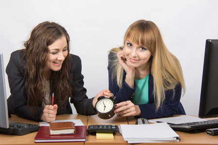 slacker: Two girls in the office happily waiting for the end of the working day Stock Photo