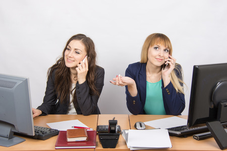 phone calls: Two young office employee talking on mobile phones at his desk
