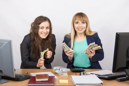 collaborators: for office table two women collaborators happily hold hands in a pack with the money and express a strong admiration Stock Photo