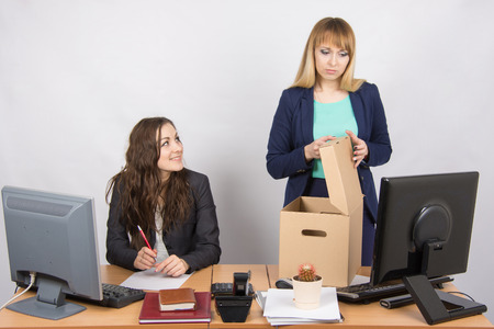 enmity: Office staff member with a smile, watching as a dismissed colleague collects things Stock Photo