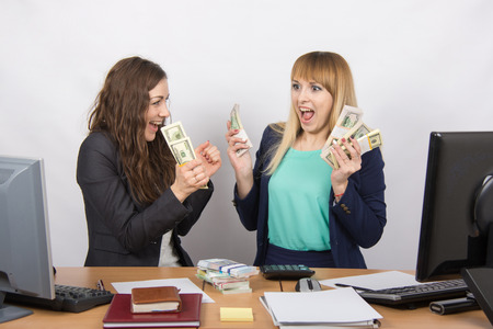 collaborators: for office table two women collaborators happily hold hands in a pack with the money and express strong Stock Photo
