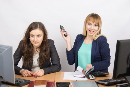 communicative: Joyful girl in the office with a phone in his hand close to the unhappy colleague
