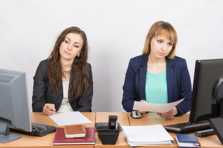 downtrodden: Employees of the office sitting at a desk with a view of the downtrodden