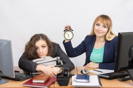 deficiencies: The girl in the office with a smile shows the time on the clock next to the exhausted colleague