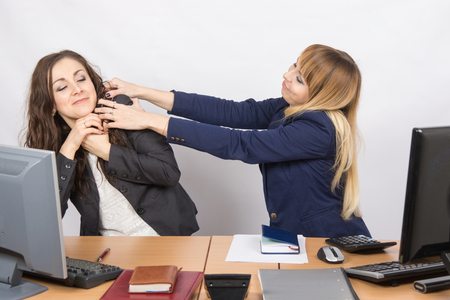 stifle: The girl in the office workplace trying to stifle a colleague Stock Photo