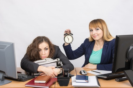 opposed: Two girls in the office at the end of the day, one with a smile, holding a clock, another weary lies on folders