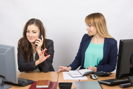 important phone call: The girl in the office talking on the phone asking a colleague to wait