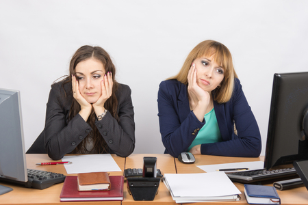 Two young office worker tired of sitting in front of computers