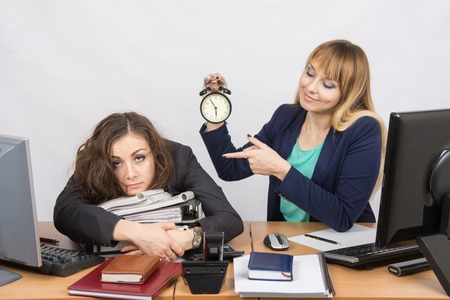 deficiencies: The girl in the office with a smile, holding a clock and looking at the tormented colleague
