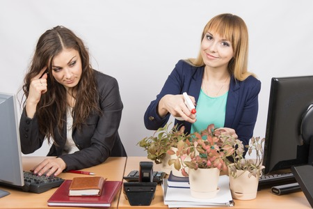considers: Office employee considers crazy colleague - a lover of flowers Stock Photo