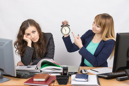 deficiencies: Office workers at the end of the day, one with a smile indicates a clock, another weary head props