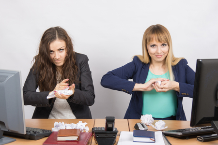 scheming: Employees of office paper crumpling up to something