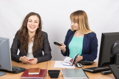 sociability: Office colleagues girl sitting at a desk and talking happily