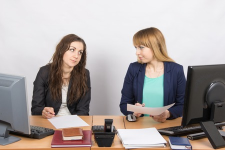 Two office employee sitting at a desk and a hostile look at each other Stock Photo
