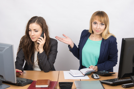 grouchy: The girl in the office puzzled indicates colleague talking on the phone