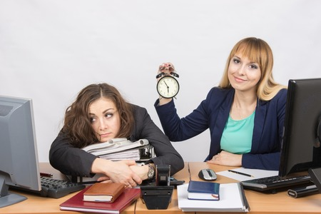 deficiencies: Two girls in the office at the end of the day, one positive, the other exhausted Stock Photo