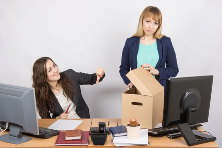 enmity: Office woman with a humiliating gesture unsettled the dismissed colleague