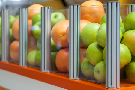 positioned: Glass showcase with fresh fruit apples and oranges, focus is positioned on apples