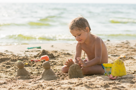enthusiasm: The child sits on the sandy beach of the reservoir and enthusiasm molds of sand cakes