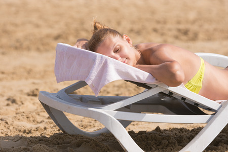 asleep chair: Young girl is lying on a deck chair on his stomach, his head turned and eyes closed