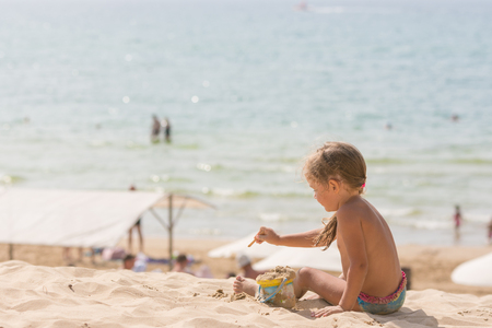 five year old: The little five year old girl sitting on the beach and playing with sand and toys on the background of the sea Stock Photo