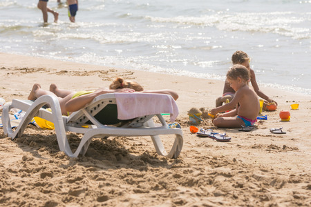 On the sea beach near the water with sunbathing chaise longue Woman and children playing in the sand