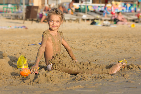 daubed: Satisfied six year old girl sitting on the beach and daubed themselves with wet sand
