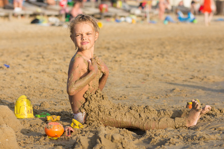 daubed: Six-year girl daubed themselves with wet sand on the beach with a sour face