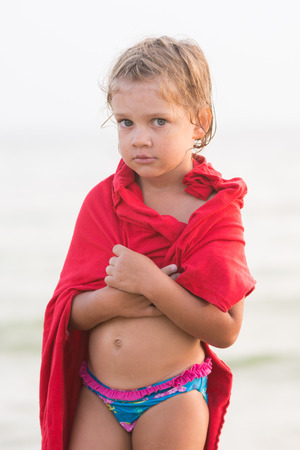five year: Sad frozen five year old girl wrapped herself in an adult t-shirt