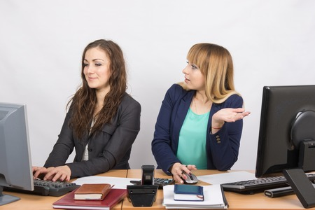 deceptive: Office worker with indignation looking at quite a colleague sitting next to a computer Stock Photo
