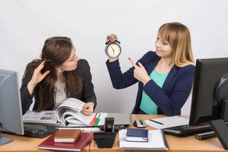 slacker: Girl shows a colleague in the office the rest of the working time on the clock