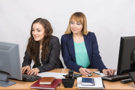 deceptive: Office worker on the sly looks at the monitor unsuspecting colleagues